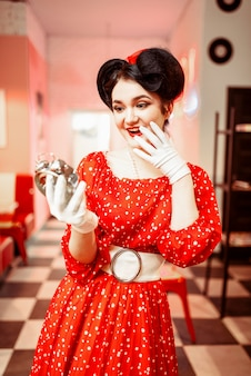 Ragazza pin up sorpresa guarda la sveglia, interni caffè vintage