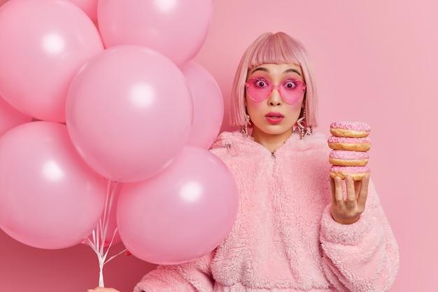 La giovane donna asiatica sorpresa dai capelli rosa sembra sorprendentemente indossa una pelliccia che tiene una pila di deliziose ciambelle e palloncini arriva alla festa rimanendo scioccata da qualcosa