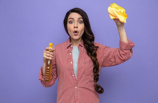 Donna delle pulizie piuttosto caucasica sorpresa che tiene in mano panni per la pulizia e detergente spray