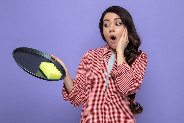 Donna pulita piuttosto caucasica sorpresa che tiene e guarda la spugna sul piatto e le mette la mano sul viso