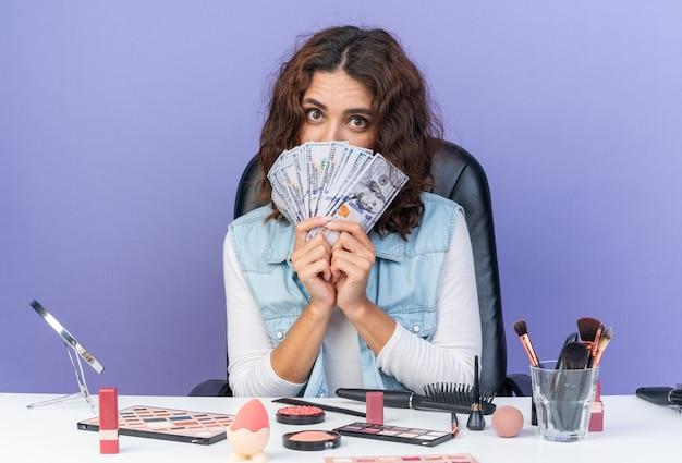 Donna abbastanza caucasica sorpresa che si siede alla tavola con gli strumenti di trucco che tengono soldi isolati sulla parete porpora con lo spazio della copia