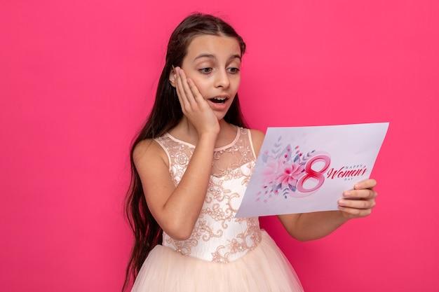 Sorpresa mettendo la mano sulla guancia bella bambina il giorno delle donne felici tenendo e leggendo il biglietto di auguri