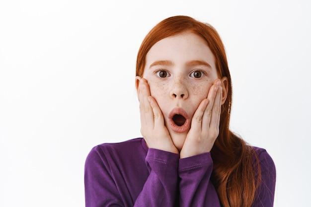 Bambina rossa sorpresa con le lentiggini che ansimano, dicendo wow e guardando stupita impressionata davanti, in piedi sul muro bianco