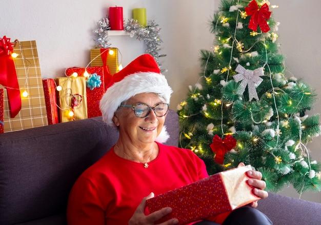Donna anziana sorpresa con cappello da babbo natale mentre apre il suo regalo di natale - albero di natale decorato e regali per la famiglia in background