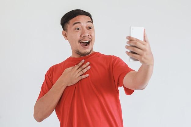 Uomo asiatico sorpreso e scioccato in maglietta rossa utilizzando smartphone su sfondo bianco white