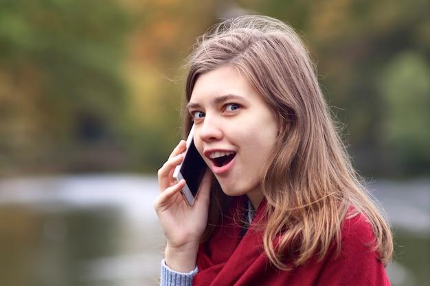 Giovane donna felice scioccata sorpresa che parla sul telefono astuto mobile delle cellule all'aperto nel parco di autunno con