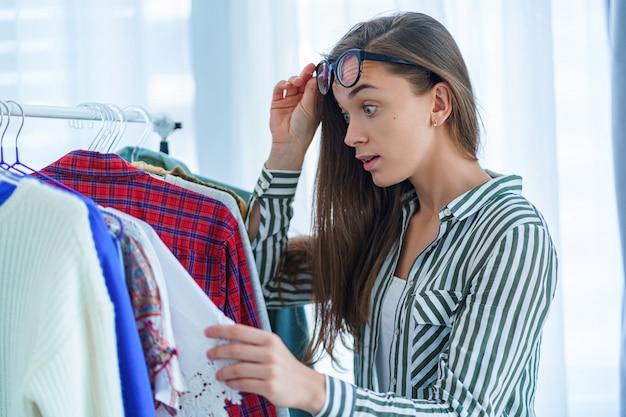 Donna sorpresa scioccata con gli occhi spalancati guardando l'etichetta di cartellino del prezzo elevato su abiti di lusso femminile costosi durante l'abbigliamento shopping e scegliendo vestito da acquistare presso il negozio di stoffa