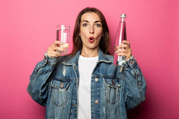 Giovane donna scioccata sorpresa che tiene un bicchiere d'acqua e una bottiglia d'acqua sulla superficie rosa