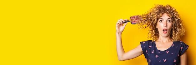 Giovane donna colpita sorpresa con il pettine aggrovigliato in capelli ricci su fondo giallo bandiera.