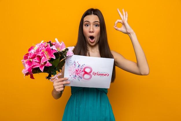 Sorpreso che mostra gesto ok bella ragazza il giorno delle donne felici che tiene biglietto di auguri con bouquet
