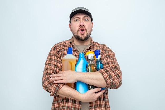 Uomo delle pulizie slavo sorpreso che tiene in mano spray e liquidi per la pulizia