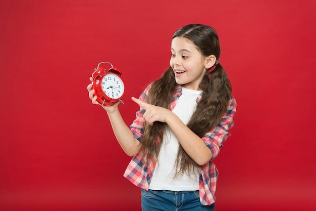Ragazza teenager sorpresa che mostra il tempo sulla sveglia retrò, le vendite dello shopping.