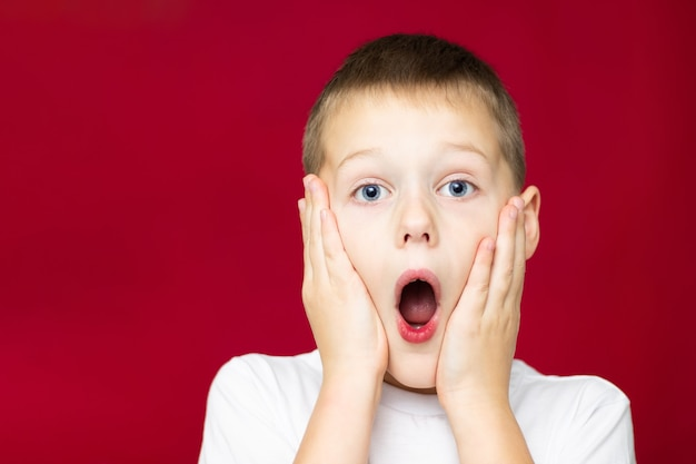 Adolescente sorpreso 7-10 in maglietta bianca, con la bocca aperta e le mani sulle guance su sfondo rosso