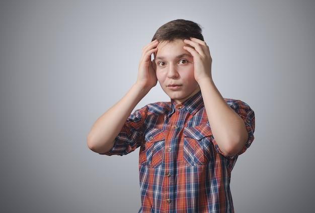 Adolescente sorpreso sulla superficie grigio-bianca che tiene la sua testa. vestito con una camicia a quadri