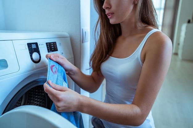 Sorpresa moglie stressata turbata trovata sul colletto della camicia di suo marito segni di rossetto rosso femminile durante il bucato