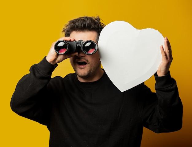 Ragazzo bianco sorpreso con mockup a forma di cuore e binocolo