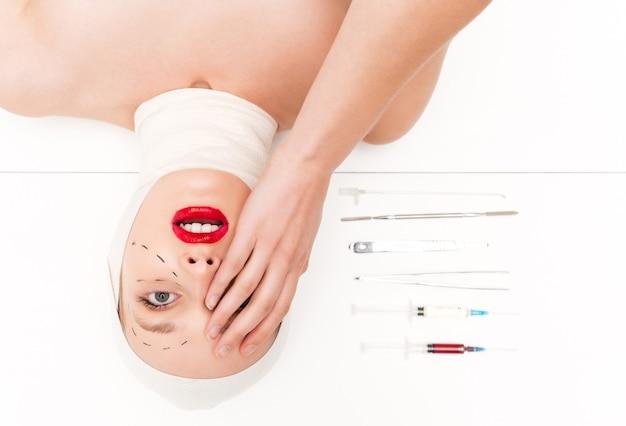 La donna sorpresa in bende ha isolato il fondo bianco con la testa sopra i talloni degli strumenti chirurgici