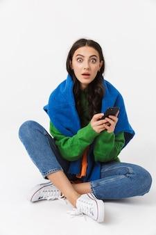 Donna sorpresa in abiti colorati, seduta sul pavimento e utilizza lo smartphone, isolato su bianco