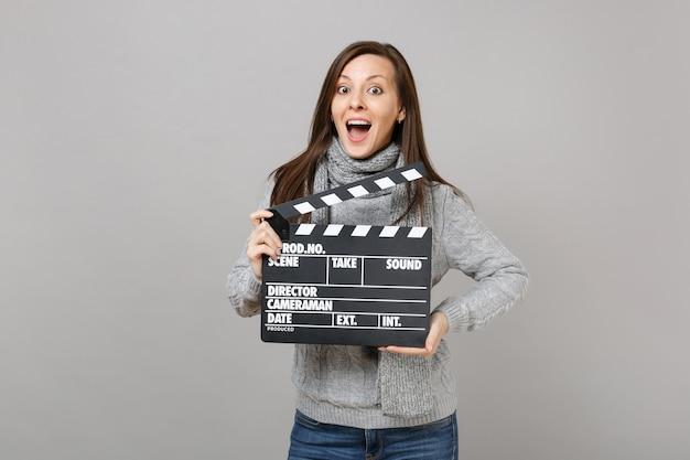 Donna sorpresa in maglione grigio, sciarpa che tiene la bocca spalancata tenere classico film nero che fa ciak isolato su sfondo grigio. stile di vita sano, emozioni delle persone, concetto di stagione fredda.