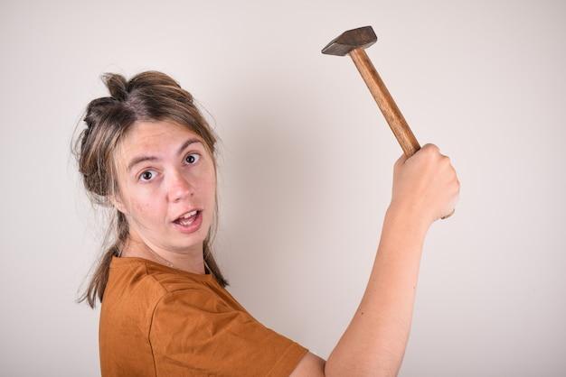 Donna sorpresa che tiene un martello tra le mani, che non sa come fare le riparazioni in casa. la donna con un martello è sorpresa dalla domanda. il concetto della scelta dei materiali da costruzione