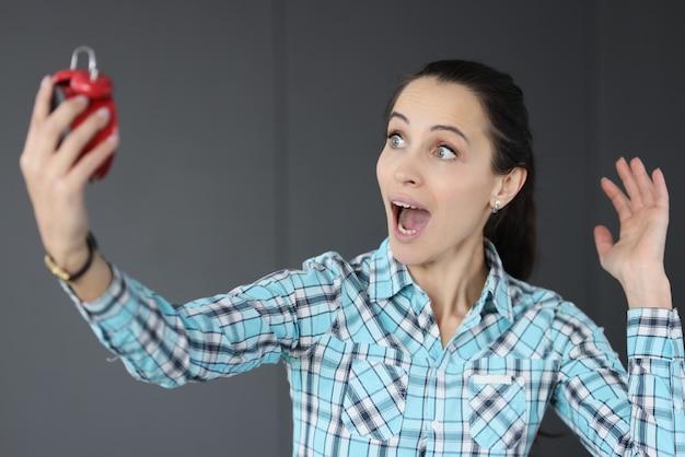 Donna sorpresa che tiene sveglia rossa nelle sue mani. concetto di gestione del tempo
