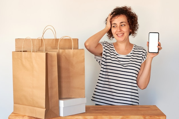 Donna sorpresa che tiene uno smartphone accanto alle borse della spesa