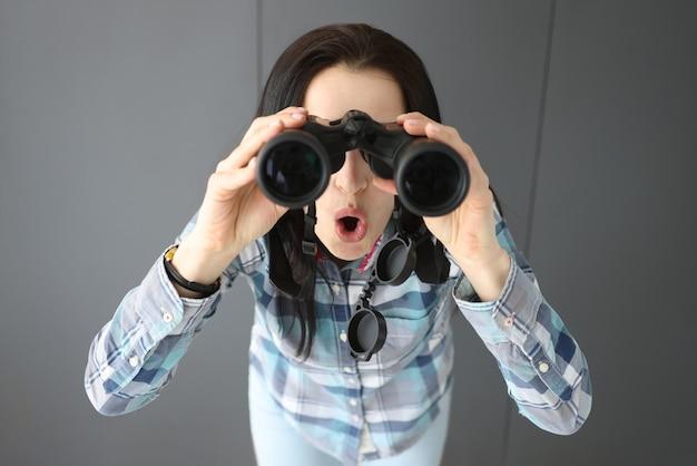 Donna sorpresa che apre la bocca e guarda attraverso un binocolo professionale nero