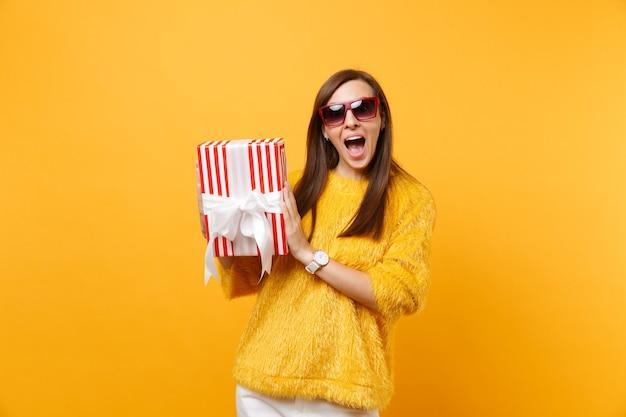 Donna sorpresa in occhiali rossi che tiene scatola rossa con regalo presente celebrando, godendosi la vacanza isolata su sfondo giallo brillante. persone sincere emozioni, concetto di stile di vita. zona pubblicità.