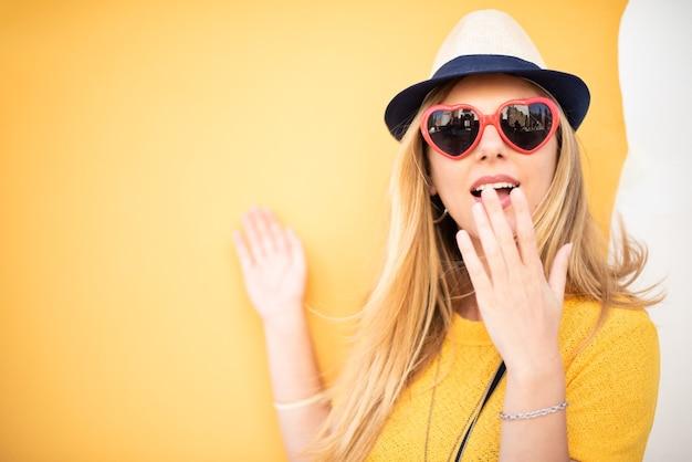 Ragazza retrò donna sorpresa con trucco labbra rosse e acconciatura moda vintage su sfondo giallo colorato da vicino