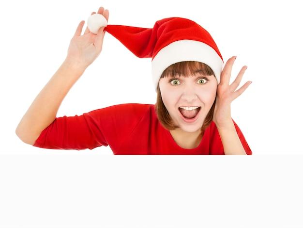 Donna sorpresa in cappello rosso della santa che tiene il pompon e che dà una occhiata da dietro il tabellone per le affissioni in bianco del segno