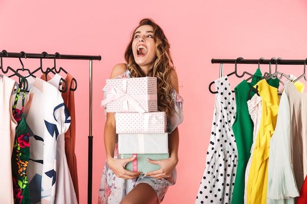 Donna sorpresa che indossa un abito in piedi in negozio vicino appendiabiti con scatole presenti isolato sul rosa
