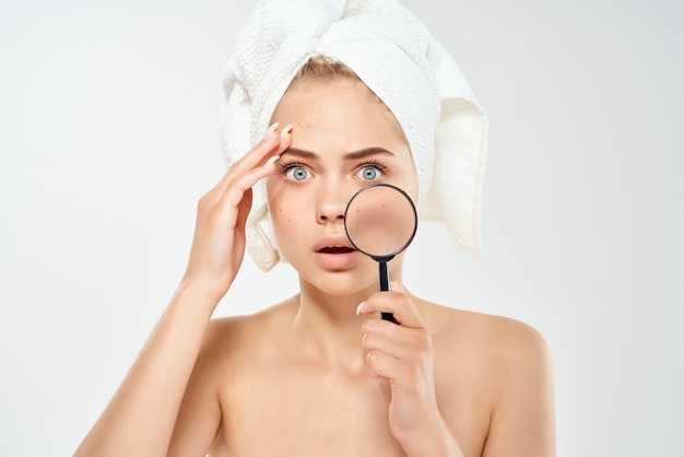 Donna sorpresa con le spalle nude pulisce la lente d'ingrandimento della pelle nei problemi di salute delle mani hands