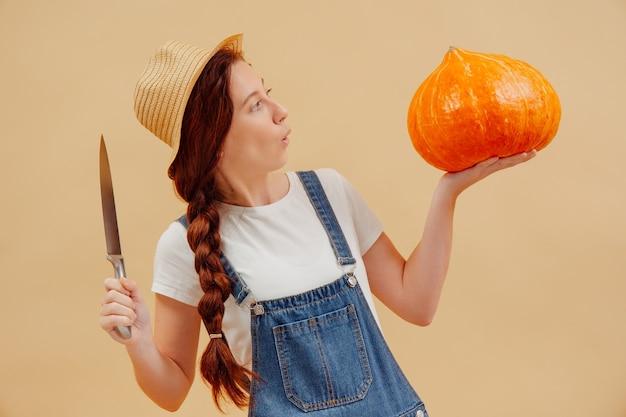 Donna sorpresa con le dimensioni di una grande zucca su uno sfondo beige con un coltello affilato