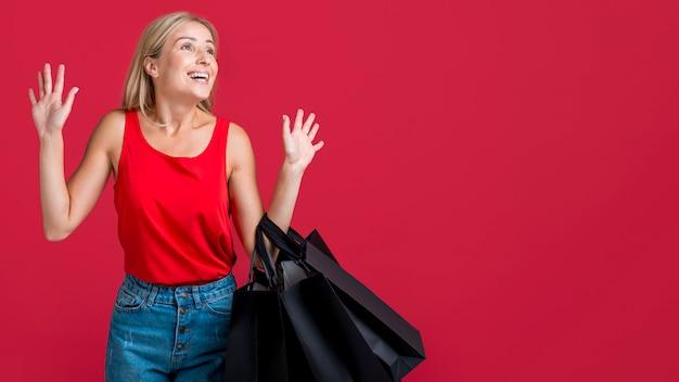 Donna sorpresa donna che tiene i sacchetti della spesa con lo spazio della copia
