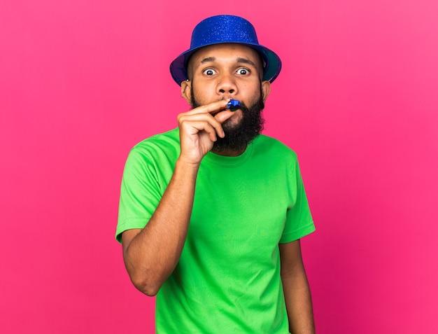 Sorpreso giovane ragazzo afro-americano che indossa il cappello da festa che soffia fischietto da festa isolato sul muro rosa