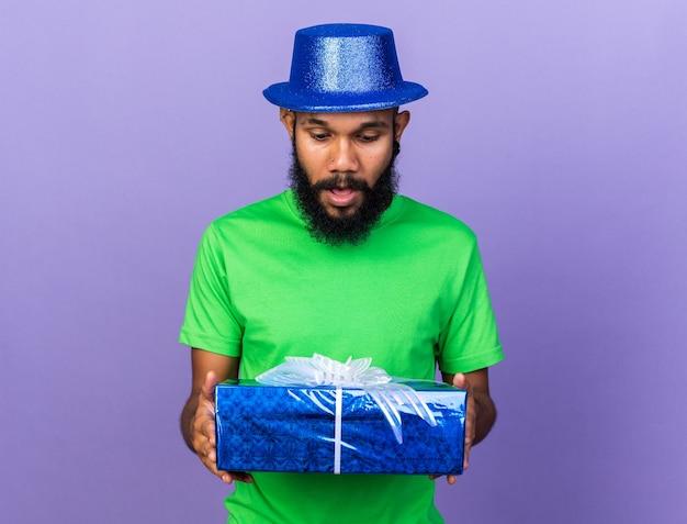 Sorpreso giovane afro-americano che indossa un cappello da festa che tiene in mano e guarda la confezione regalo isolata sulla parete blu
