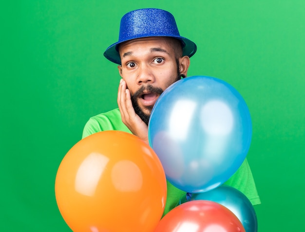 Sorpreso giovane ragazzo afroamericano che indossa un cappello da festa in piedi dietro i palloncini mettendo la mano sulla guancia isolata sul muro verde