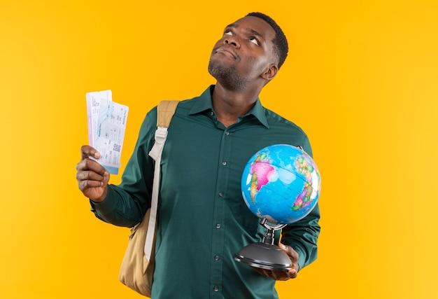Giovane studente afroamericano sorpreso con lo zaino che tiene i biglietti aerei e il globo che guarda in su