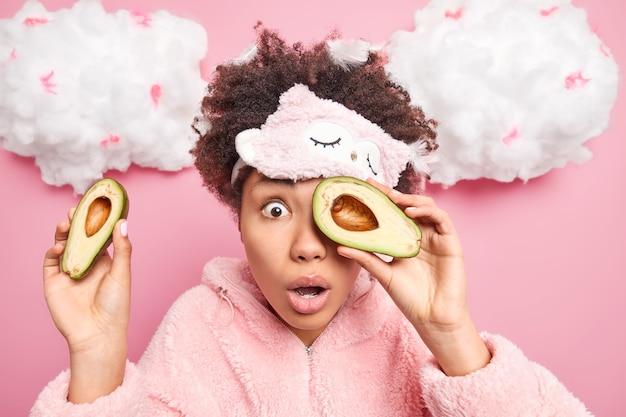 La giovane donna afroamericana sorpresa tiene metà dell'avocado sopra gli occhi fissa gli occhi spalancati indossa la maschera del pigiama si sottopone a procedure di bellezza dopo il risveglio