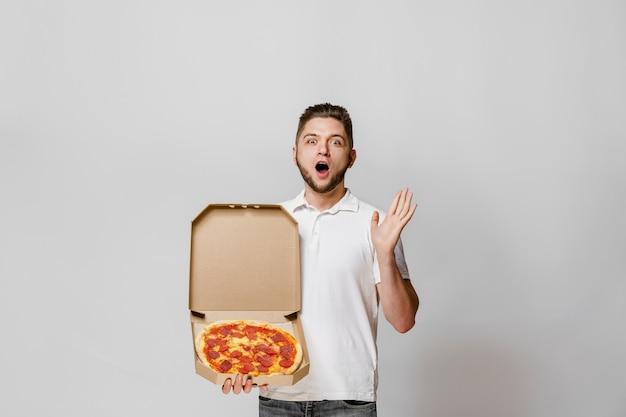 Giovane corriere barbuto sorpreso con pizza in una scatola di cartone in mano