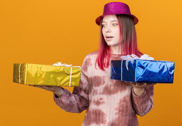 Giovane bella ragazza sorpresa che indossa un cappello da festa che tiene in mano e guarda le scatole regalo