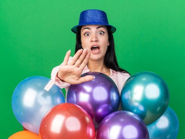 Sorpresa giovane bella ragazza che indossa un cappello da festa in piedi dietro i palloncini che porge la mano alla telecamera