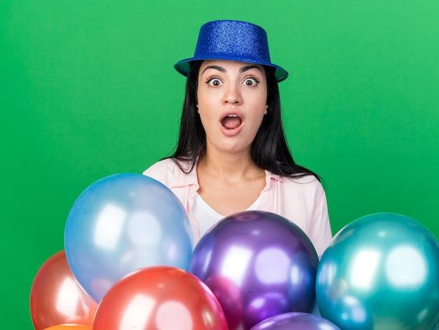 Sorpresa giovane bella ragazza che indossa un cappello da festa in piedi dietro i palloncini