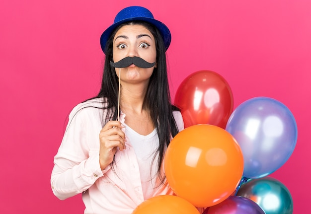 Sorpresa giovane bella donna che indossa un cappello da festa con palloncini che tengono baffi finti su un bastone isolato su una parete rosa