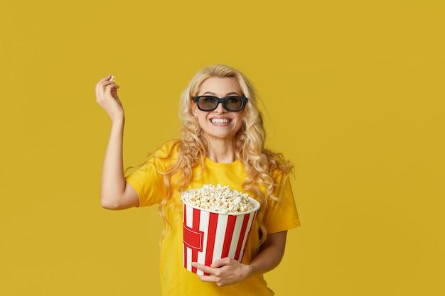 La giovane donna bionda sorpresa in vetri 3d e la camicia gialla che mangiano il popcorn, sembra il film scioccante al cinema. isolato