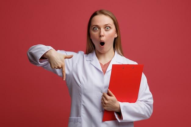 Giovane medico femminile biondo sorpreso che porta veste e stetoscopio medici intorno alla lavagna per appunti della tenuta del collo rivolta verso il basso