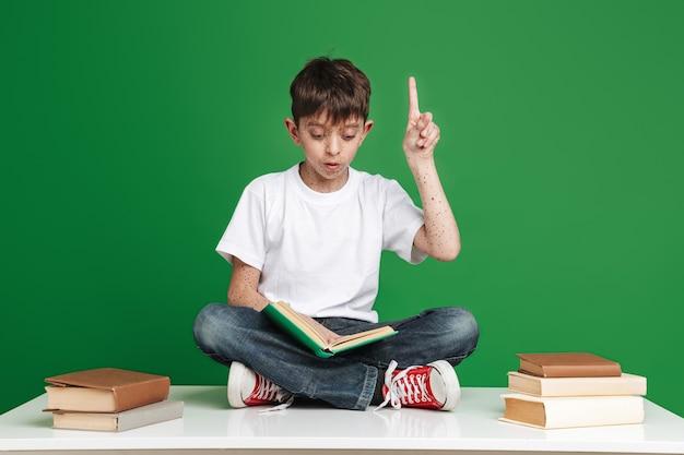 Ragazzo sorpreso con le lentiggini che legge un libro e che ha un'idea sul muro verde