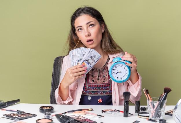 Giovane ragazza castana sorpresa che si siede alla tavola con gli strumenti di trucco che tengono soldi e sveglia che osserva in su isolato sulla parete verde oliva con lo spazio della copia