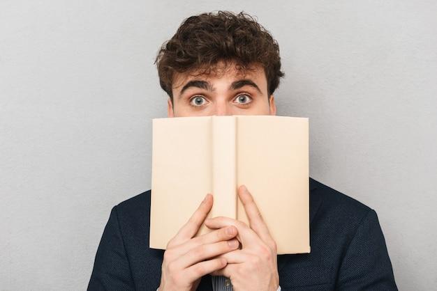 Giovane imprenditore sorpreso che indossa tuta in piedi isolato su grigio, coprendosi il volto con un libro