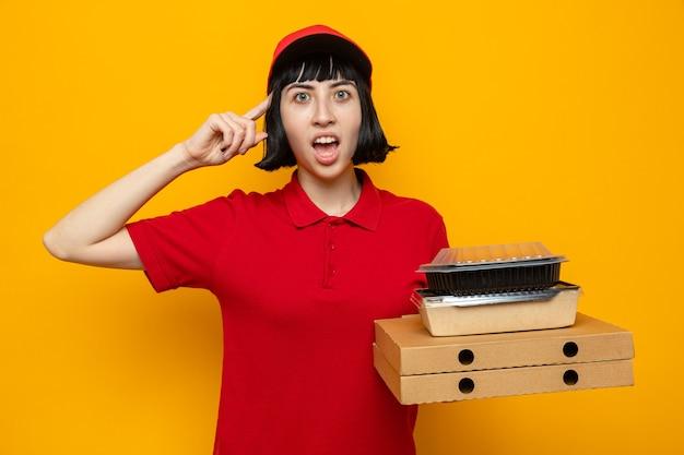 Giovane ragazza delle consegne caucasica sorpresa che tiene contenitori per alimenti su scatole per pizza